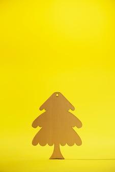 Деревянная рождественская елка на желтом фоне с копией пространства.