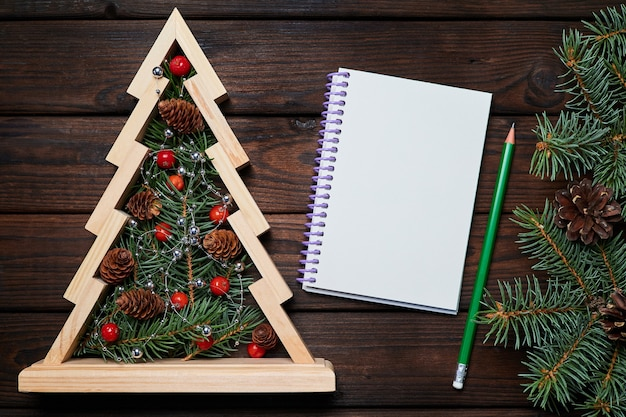 Wooden christmas tree with fir branches inside and a blank notepad on wooden background
