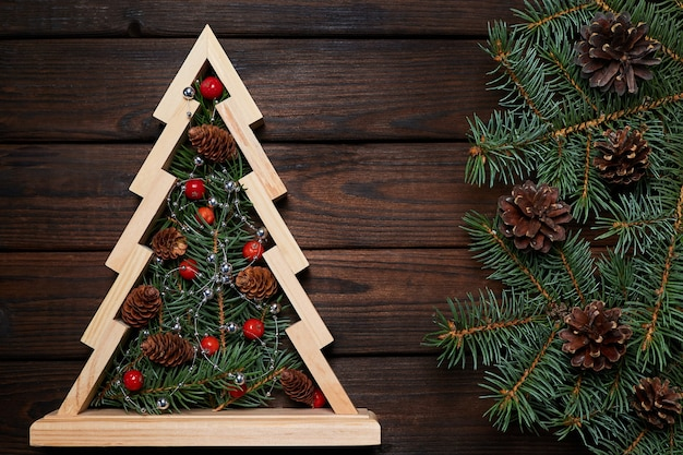 Wooden christmas tree with fir branches inside decorated with rowan berries and cones