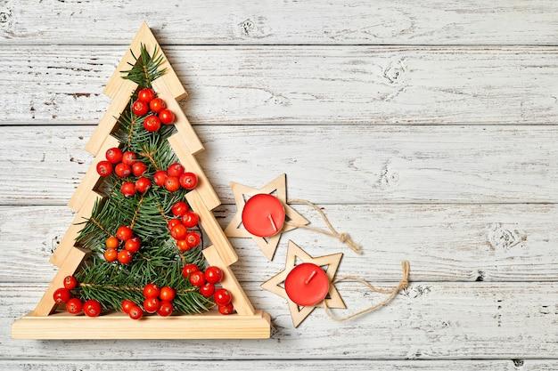 ナナカマドの果実の星とキャンドルで飾られた内部にモミの枝を持つ木製のクリスマスツリー