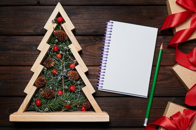 Wooden christmas tree with fir branches inside gift boxes with red ribbons and a blank notepad