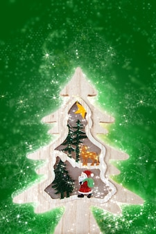 Wooden christmas tree with lights on green background.