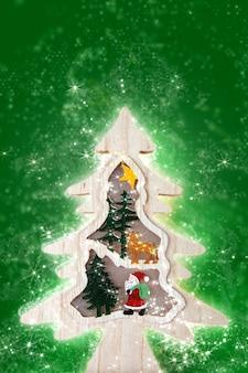 緑の背景にライトと木製のクリスマスツリー。