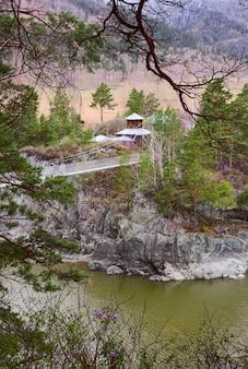 緑の水に架かるカトゥン吊橋の急な岩の多い海岸にある木造教会