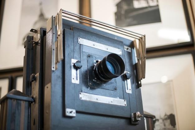 Деревянный классический ретро фотоаппарат на штативе.