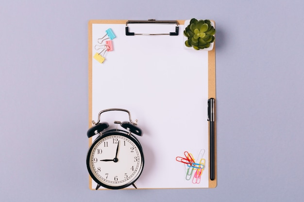 Of wooden clipboard with blank paper, pen, stationery and alarm-clock on light grey background.  free space. copy space. top view.