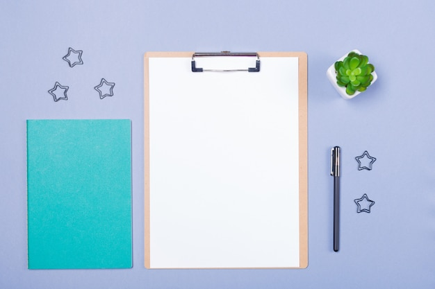 Of wooden clipboard with blank paper and stationery on light grey background.  free space. copy space. school concept. workplace. desk top.