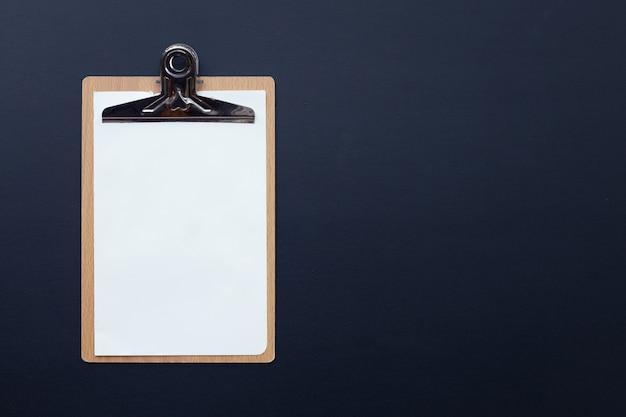 Деревянный буфер обмена с пустой белой бумагой на темном фоне.
