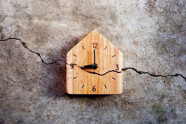 Wooden clock on cracked cement wall. top view