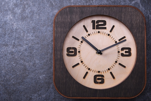 Wooden clock handmade on wooden table. close-up.