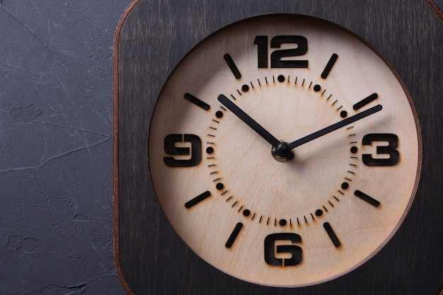 Wooden clock made in hand on wooden table. close-up. place for a text.