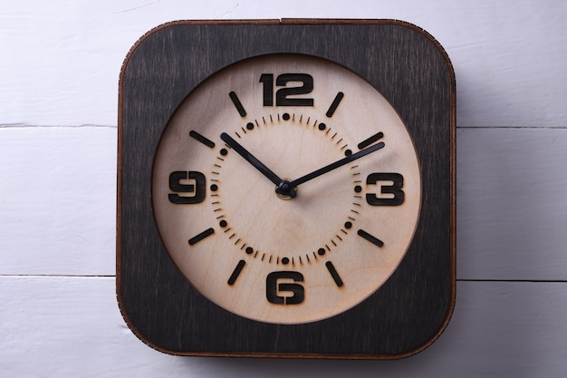 Wooden clock made in hand on wooden table. close-up.