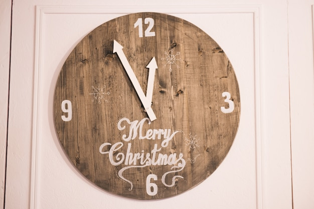 Wooden clock on a white background with the inscription merry christmas, the hands beat midnight