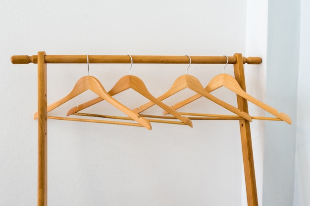 Wooden clothes hanger on line with white wall background interior.