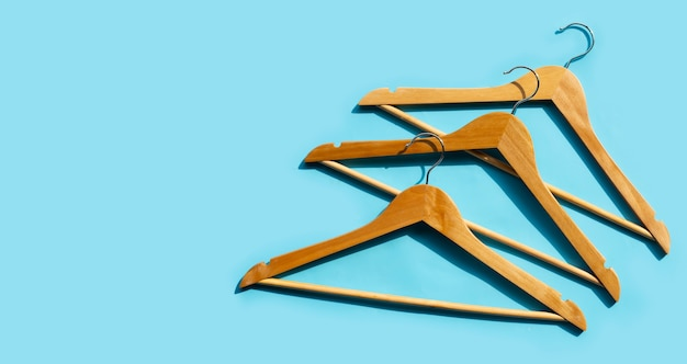Wooden clothes hangers on blue surface