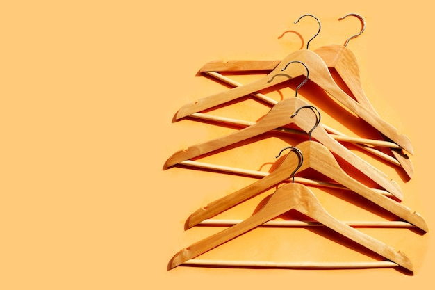 Wooden clothes hangers on yellow surface