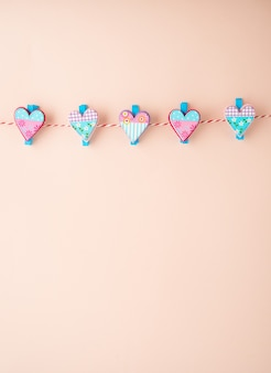 Wooden clothespin with small hearts on the pastel background, copy space