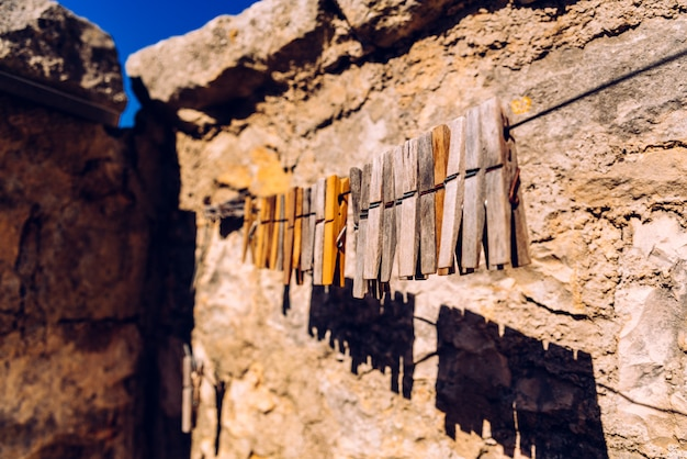 Wooden clothespins for hanging clothes with aged stone rural background.