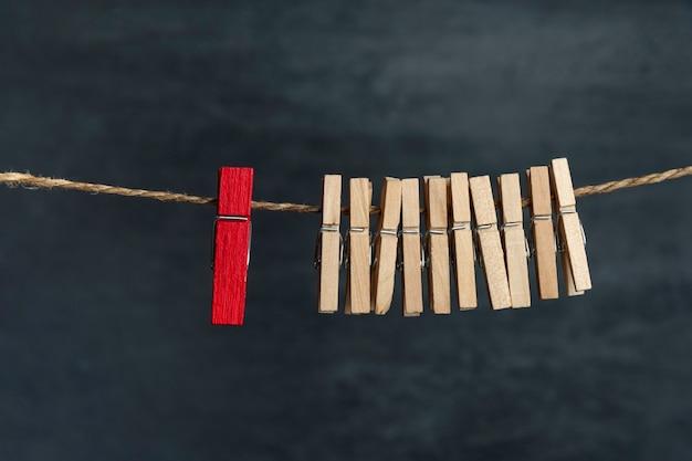 Деревянные прищепки на веревке и одна красная. отличие от других. отдельно от толпы. концепция лидерства.