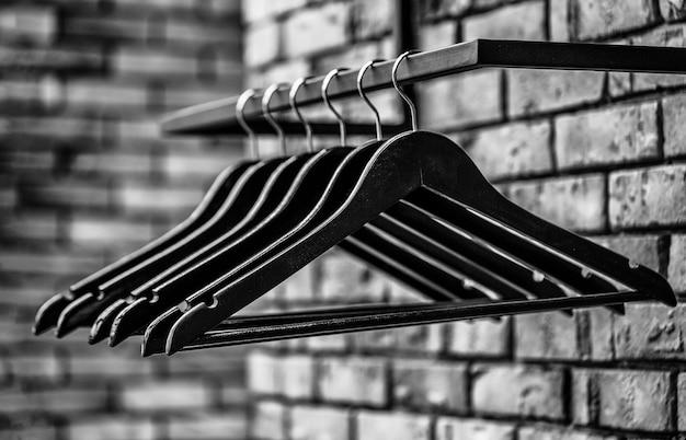 나무 옷걸이 옷. 유행 다른 유형의 옷걸이. 막대에 많은 나무 검은 옷걸이. 상점 개념, 판매, 디자인, 빈 옷걸이. 검정색과 흰색.