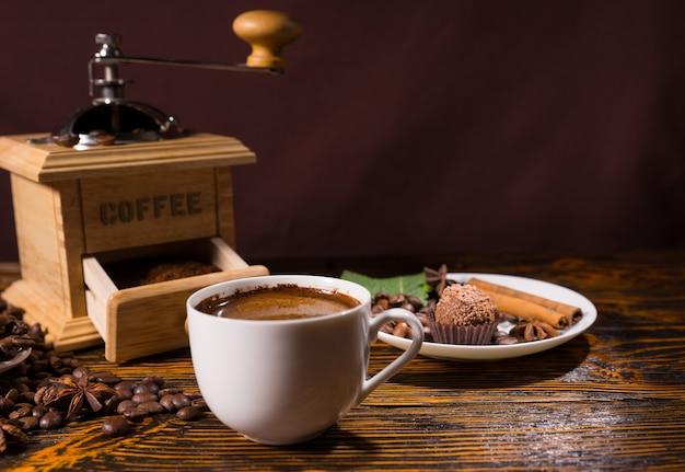 白いマグカップと御馳走による木製のコーヒーグラインダー
