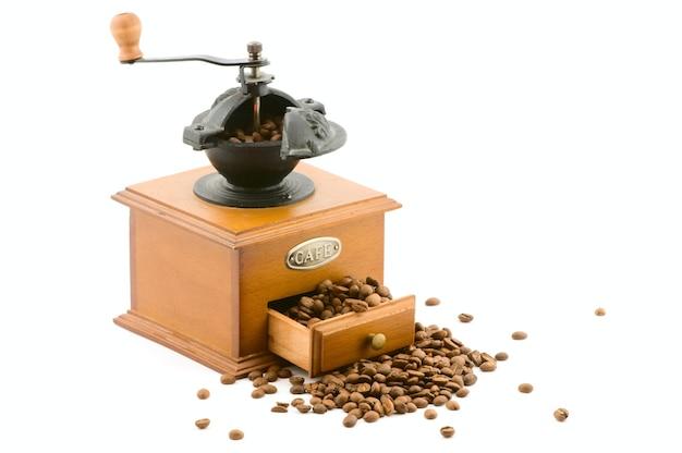 白で隔離される豆の木製コーヒーグラインダー