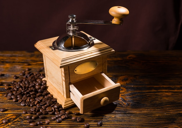Wooden coffee grinder with scattered beans