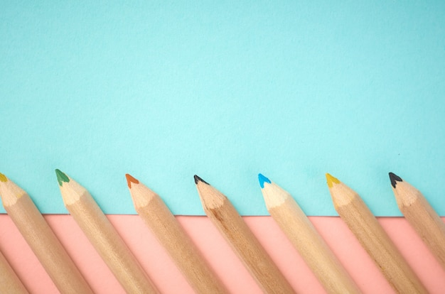 Wooden color pencils on blue and pink background with copyspace, flat lay