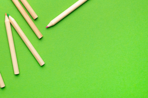 Wooden colored pencils and green background, office for children and adults