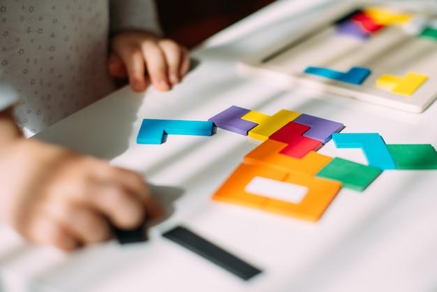 Деревянная разноцветная головоломка лежит на столе возле малыша.