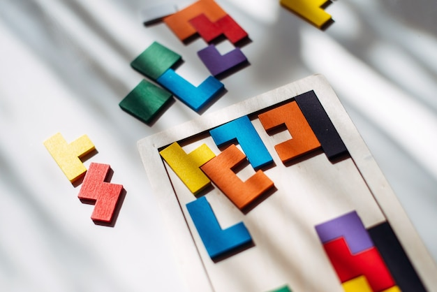 На столе разбросана деревянная разноцветная головоломка.