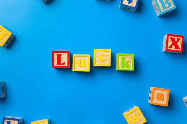 Wooden colorful alphabet blocks on blue background