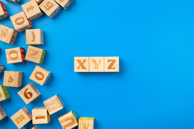 Wooden colorful alphabet blocks on blue