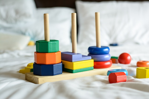 Wooden colorful blocks and sorting shapes on the bed