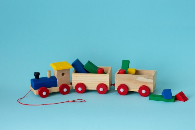 Wooden colorful toy train with details on a soft blue