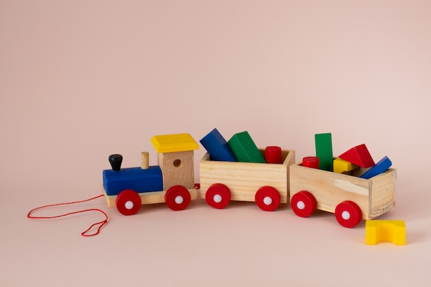 Wooden colorful toy train with details on a soft pink