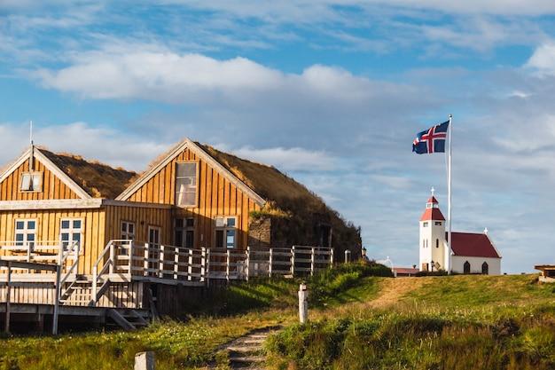 깃발과 교회가있는 아이슬란드 캠프장의 목조 건축