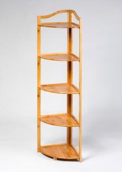 Wooden corner shelves unit isolated on gray background
