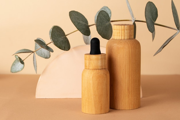 Wooden cosmetics containers on the pastel background.geometrical podium and fresh eucalyptus branch behind.earth colors,zero waste containers.mockup concept.
