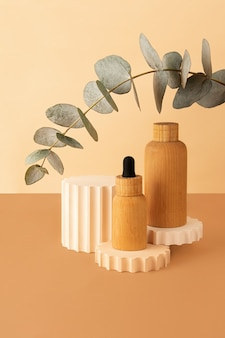 Wooden cosmetics containers on the pastel isometric background.geometrical podium and fresh eucalyptus branch behind.earth colors,zero waste containers.mockup concept.