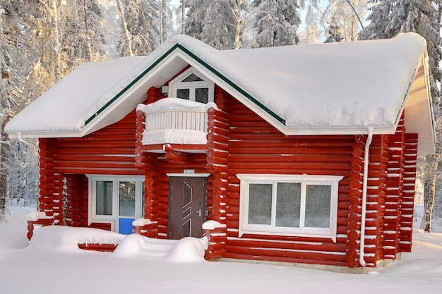 昼間の雪に覆われた冬の森を背景に雪に覆われた屋根のある、赤く塗られた丸太の木造コテージ。
