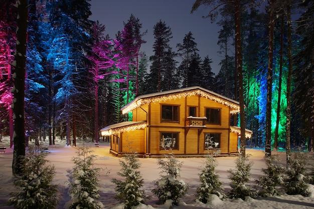 눈 덮인 겨울에 크리스마스 장식이 있는 나무 오두막. 집 근처 숲에 밝은 조명이 있는 나무.