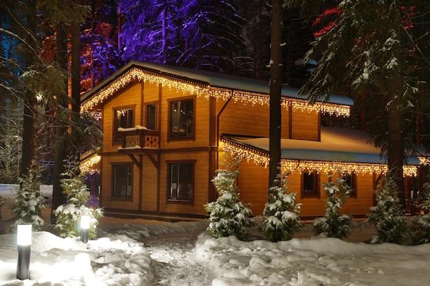 눈 덮인 겨울에 크리스마스 장식이 있는 나무 오두막.