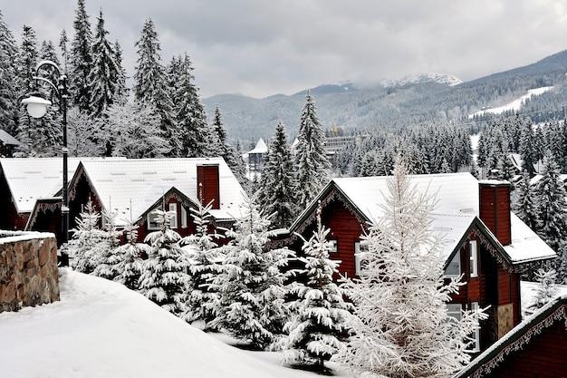 산악 휴양지의 목조 별장은 겨울에 신선한 눈으로 덮여 있습니다.
