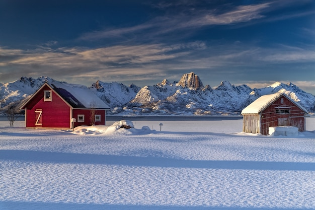 Wooden cottages on a snow covered field surrounded by snow covered mountains in norway