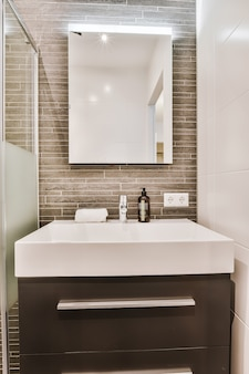 Wooden countertop with white basin near shower cabin with glass wall and mirror in bathroom