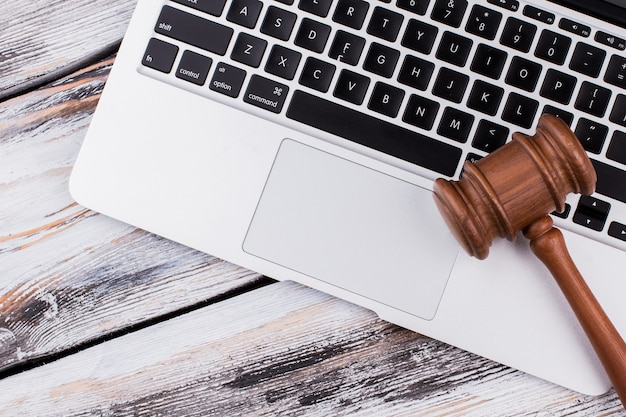 Деревянный молоток суда на клавиатуре ноутбука. старый белый деревянный стол.
