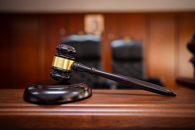 Деревянный молоток суда на деревянном столе в зале суда, судьи и суде. аукцион. закон и справедливость, понятие законности, судья.
