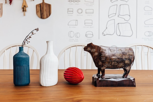 Wooden cow sculpture with cut of meat beef of diagram on it with blue, white jar and red fruit on wooden table.