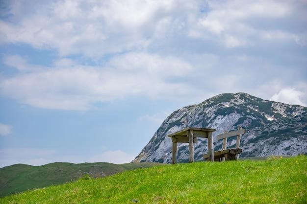 Деревянные уютные скамейки расположены на склоне живописной горы.